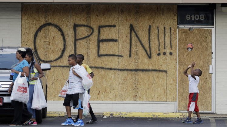 FILE - In this Aug. 18, 2014 file photo, a young boy tosses a football as people walk past a business boarded up to protect against looting in Ferguson, Mo. The unmistakable signs of healing are beginning to dot Ferguson, even the small area of town that has been the center of the world's attention. But those in the community know they've got a long way to go. (AP Photo/Jeff Roberson, File)