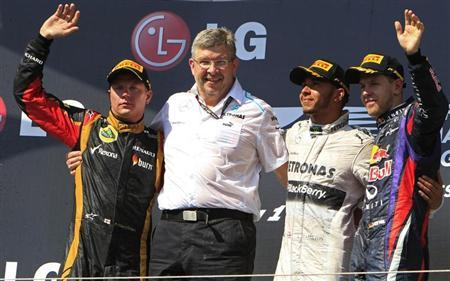Mercedes' Hamilton poses with team principal Brawn, Lotus F1's Raikkonen and Red Bull's Vettel on the podium after winning the Hungarian F1 Grand Prix in Mogyorod