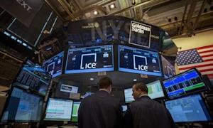 Traders work at the Goldman Sachs post that trades IntercontinentalExchange on the floor of the NYSE