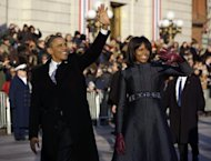 President Barack Obama and first lady Michelle Obama waves as they walk down Pennsylvania Avenue near the White House during the 57th Presidential Inauguration parade Monday, Jan. 21, 2013, in Washington. (AP Photo/Charles Dharapak)