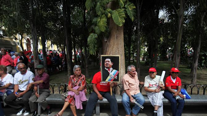 A supporter of Venezuela's President Hugo Chavez holds a poster of him outside the National Assembly in Caracas, Venezuela, Saturday, Jan. 5, 2013. Venezuelan lawmakers are meeting Saturday to select a new president of the National Assembly in a session that could give clues to the future of the country amid uncertainty about ailing Chavez. National Assembly President Diosdado Cabello opened the session and Vice President Nicolas Maduro also attended the meeting. (AP Photo/Fernando Llano)