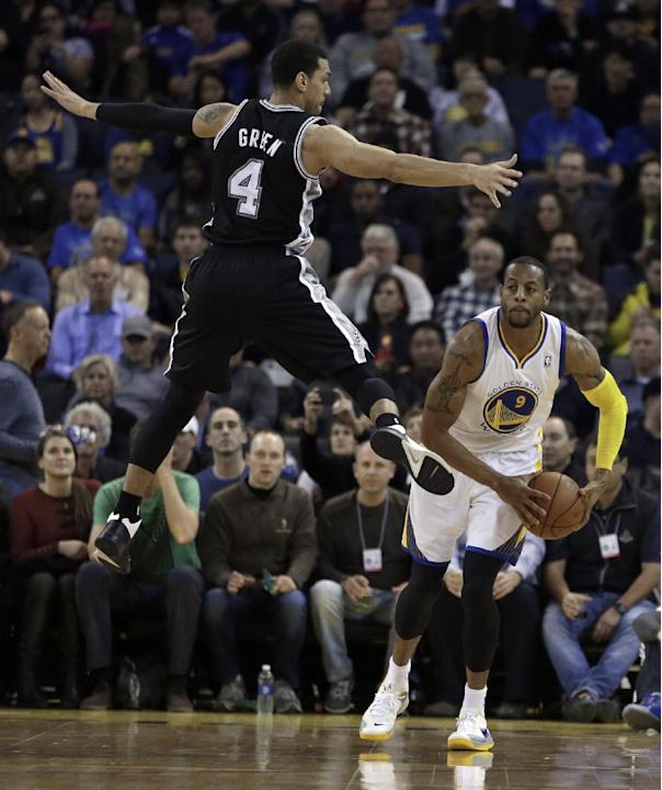Golden State Warriors' Andre Iguodala, right, looks to pass away from San Antonio Spurs' Danny Green (4) during the first half of an NBA basketball game, Thursday, Dec. 19, 2013, in Oakland, C