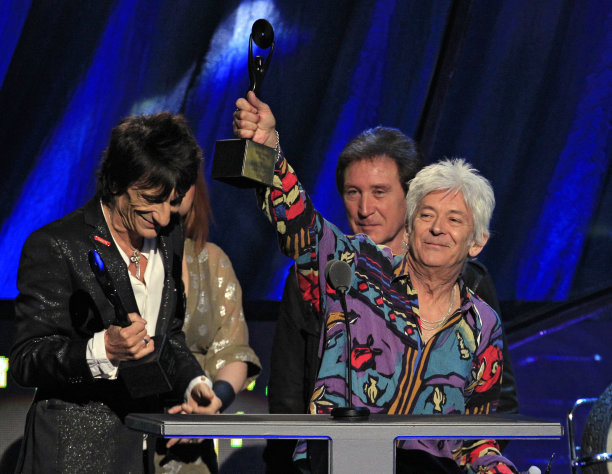 Ian McLagan, right, holds up his trophy after he and Ron Wood, left, and Kenney Jones, background, were inducted into the Rock and Roll Hall of Fame as members of the Small Faces/Faces Saturday, April 14, 2012, in Cleveland. (AP Photo/Tony Dejak)