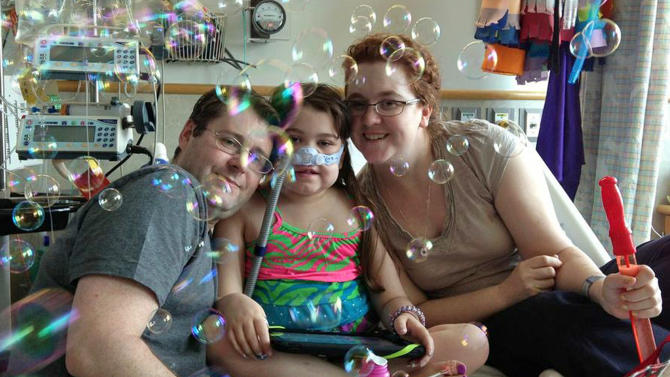 FILE - In this May 30, 2013 file photo provided by the Murnaghan family, Sarah Murnaghan, center, celebrates the 100th day of her stay in Children's Hospital of Philadelphia with her father, Fran, left, and mother, Janet. The national organization that manages organ transplants on Monday June 10, 2013 resisted making emergency rule changes for children under 12 who are waiting on lungs but created a special appeal and review system to hear such cases. (AP Photo/Murnaghan Family, File)