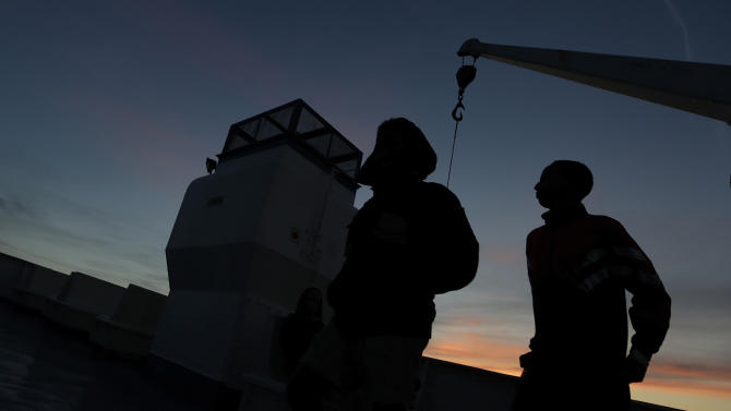 Amsa, 16 years-old, last name not available, a migrant from Somalia, right, watches the sunset as he leaves aboard a ferry the Sicilian Island of Lampedusa, Monday, Oct. 7, 2013. Italian divers recovered 17 more bodies Monday from a smugglers' boat that capsized and sank to bottom of the Mediterranean Sea with hundreds of migrants on board. That brought the confirmed death toll from Thursday's tragedy to 211 before poor weather off the southern island of Lampedusa again halted the recovery operation. Only 155 people of the estimated 500 on board survived the sinking. Scores of bodies are believed to be still trapped in the hull of the 18-meter (59-foot) boat, which is resting 47 meters (154 feet) below the surface. Monday was the first day that divers entered the hull. Coast Guard Capt. Filippo Marini estimated it would take two more days to complete the search and recovery mission. (AP Photo/Luca Bruno)