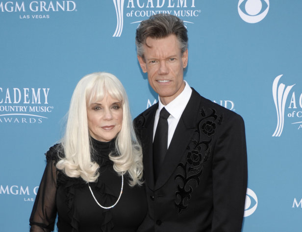 FILE - In this April 18, 2010 file photo, country singer Randy Travis, right, and then wife Elizabeth arrive at the 45th Annual Academy of Country Music Awards in Las Vegas. Travis has been sued by his ex-wife and former manager Elizabeth Travis for breaking his management contract. She says he hired an armed guard and several men to strip her three=story office building of all records and memorabilia pertaining to him. (AP Photo/Dan Steinberg, file)