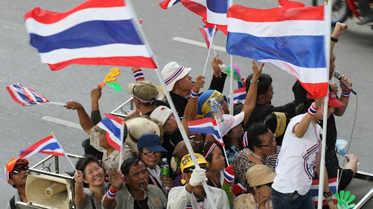 """Anti-government protesters riding on a truck wave Thai national flags on their way to the Industry Ministry in Bangkok, Thailand, Wednesday, Nov. 27, 2013 Protesters vowing to topple Thai Prime Minister Yingluck Shinawatra took to the streets for a fourth straight day on Wednesday, declaring they would take over """"every ministry"""" of the government. The brash threat is the biggest challenge yet to the embattled premier's administration, raising fears of fresh political violence in the Southeast Asian nation. (AP Photo/Sakchai Lalit)"""
