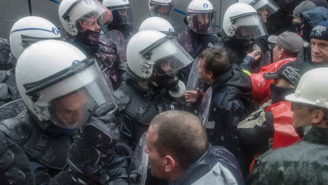 Steel workers from ArcelorMittal in Liege, Belgium, face riot police during a protest near to regional government offices in Namur, Belgium, on Tuesday Jan. 29, 2013. Workers seeking to get close to the offices threw bricks at police. Authorities responded with tear gas and water cannon. Police said two policemen had to be hospitalized with the others treated locally, all for minor injuries. It was unclear how many protesters were injured. The world's leading steel and mining company ArcelorMittal announced Thursday it will close a coke plant and six production lines in Belgium, in a move that threatens 1,300 jobs. (AP Photo/Geert Vanden Wijngaert)