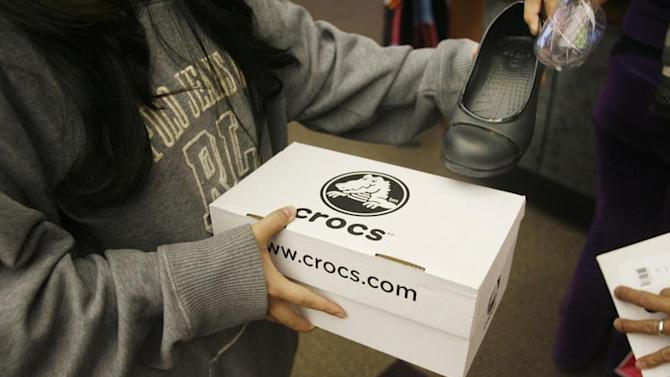 A shopper holds a box of Crocs shoes at the Glendale Galleria shopping mall on Black Friday