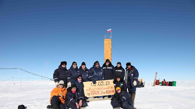"""In this Monday, Feb. 6, 2012 photo provided by Arctic and Antarctic Research Institute of St. Petersburg,   Russian researchers at the Vostok station in Antarctica pose for a picture after reaching subglacial lake Vostok. Scientists hold the sign reading """"05.02.12, Vostok station, boreshaft 5gr, lake at depth 3769.3 meters."""" Russian scientists said Monday that a new form of microbial life has been found in water samples taken from the giant freshwater lake hidden under kilometers of Antarctic ice. (AP Photo/Arctic and Antarctic Research Institute Press Service, HO)"""