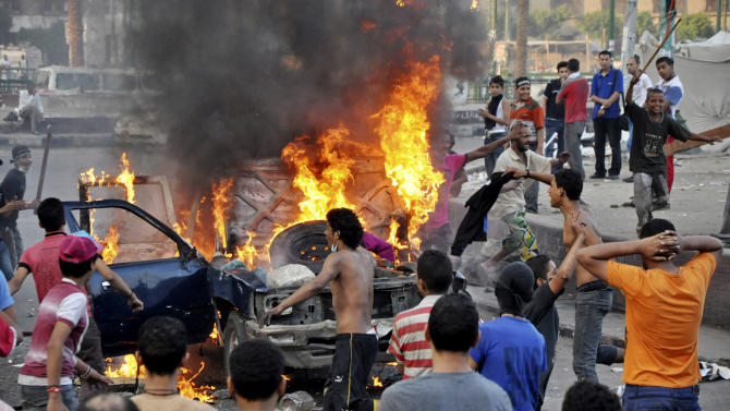 Egyptian protesters gather around a burning vehicle in downtown Cairo, Egypt, early Saturday, Sept. 15, 2012, before police cleared the area after days of protests against a film ridiculing the Prophet Muhammad. Egyptian police on Saturday cleared out protesters who have been clashing with security forces for the past four days near the U.S. Embassy as most cities around the Muslim world reported calm a day after at least six people were killed in a wave of angry protests over an anti-Islam film.(AP Photo)