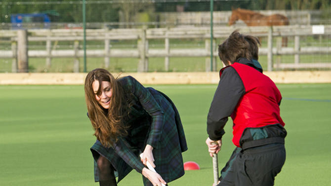 """Kate, the Duchess of Cambridge, plays hockey during her visit to St. Andrew's School, where she  attended school from 1986 till 1995, in Pangbourne, England, Friday, Nov. 30, 2012. The Duchess of Cambridge has gone back to school. The royal, formerly known as Kate Middleton, played hockey and revealed her childhood nickname — Squeak — when she returned to her elementary school for a visit Friday. Kate told teachers and students at the private St. Andrew's School in southern England that her 10 years there were """"some of my happiest years."""" She said that she enjoyed it so much that she had told her mother she wanted to return as a teacher. (AP Photo/Arthur Edwards, Pool)"""