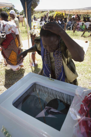 """A woman reacts after viewing the coffin of Ugandan gay activist, David Kato at Mukono, Uganda, Friday, Jan. 28, 2011. A prominent Ugandan gay rights activist whose picture was published by an anti-gay newspaper next to the words """"Hang Them"""" was bludgeoned to death. Police said Thursday his sexual orientation had nothing to do with the killing and that one """"robber"""" had been arrested. (AP Photo/Michele Sibiloni)"""