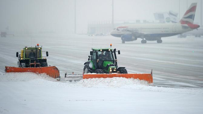 Snow ploughs clean the the tarmac of the Munich, southern Germany, airport, Monday, Jan 21, 2013. Hundreds of fights were canceled in Britain, France and Germany Monday as snow and ice blanketed Western Europe. (AP Photo/dapd, Lennart Preiss)