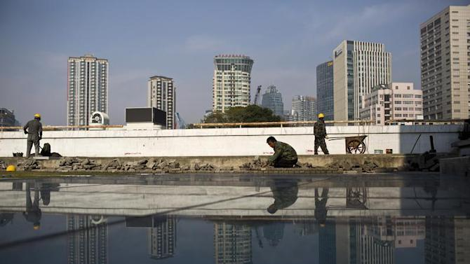 Men work at a construction site in downtown Shanghai