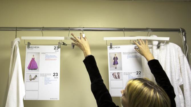 A woman puts dress diagrams on a bar backstage before a presentation of the Marchesa Autumn/Winter 2013 collection during New York Fashion Week
