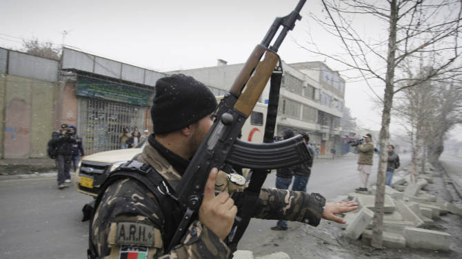 A security man with the Afghan intelligence services stops a vehicle, unseen, at the scene of a suicide car bomb attack in Kabul, Afghanistan, Wednesday, Jan. 16, 2013. Six militants — one driving a car packed with explosives — attacked the gate of the Afghan intelligence service in the capital Kabul on Wednesday, setting off a blast that could be heard throughout downtown and which sent a plume of dark smoke rising into the sky. (AP Photo/Musadeq Sadeq)