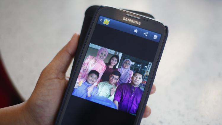 Arni Marlina shows picture of family member onboard missing Malaysia Airlines flight, at a hotel in Putrajaya