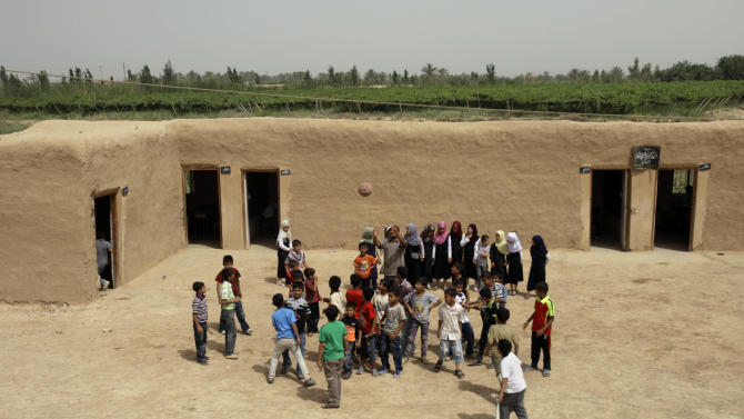 In this photo taken on Tuesday, May 15, 2012, students play during a physical class at Alhambra elementary school, made from mud, in Khalis 50 miles (80 kilometers) north of Baghdad, Iraq. Millions of dollars in international aid to build and repair Iraq's dilapidated schools have for years gone unspent. Now, Iraq's government risks losing the funding as the World Bank weighs whether some of it would be better used in some of the poorest nations around the globe. (AP Photo/Khalid Mohammed)