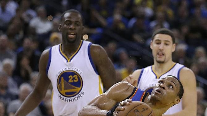 Oklahoma City Thunder guard Russell Westbrook shoots past Golden State Warriors' Draymond Green (23) and Klay Thompson during the second half of an NBA basketball game Thursday, Dec. 18, 2014, in Oakland, Calif.  The Warriors won, 114-109. (AP Photo/Ben Margot)