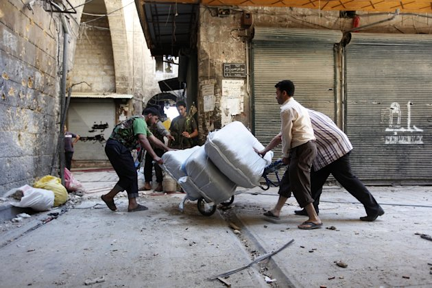 "FILE - In this Monday September 24, 2012 file photo, a Free Syrian Army fighter, left, helps traders, right, as they remove their stock from their shops, at the souk of the old city of Aleppo city, Syria. Wealthy Syrians say the violence from the 19-month civil war has pommeled their businesses, but the squeeze from a complex array of sanctions is the noose slowly strangling their country's buckling economy. They warn that if their companies tank, thousands of employees may find themselves out of work and dragged into the fighting. Today, streets are manned by checkpoints and tanks. Construction on new apartment complexes has stopped as plumes of smoke rise from the city's hard-hit suburbs. In Aleppo, bombs have ripped through the city and a more than two-month long government offensive there has not only killed hundreds of civilians, but damaged ancient sites and demolished entire neighborhoods. Arabic on the closed shop at right reads,""Aleppo."" (AP Photo/Hussein Malla, File)"
