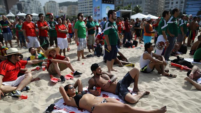 A Mexico soccer fan sunbathes as she watches her team's World Cup match with Cameroon inside the FIFA Fan fest area on Copacabana beach, in Rio de Janeiro, Brazil, Friday, June 13, 2014. (AP Photo/Leo Correa)