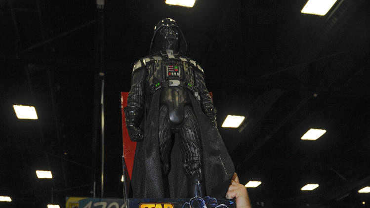 A fan carries a Star Wars Darth Vader figure he has for sale as he walks through the exhibit hall during the Preview Night event on Day 1 of the 2013 Comic-Con International Convention on Wednesday, July 17, 2013 in San Diego. (Photo by Denis Poroy/Invision/AP)