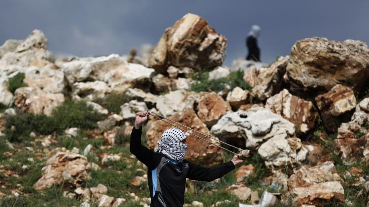 A Palestinian protester uses a sling to throw a stone towards Israeli troops during clashes at a weekly protest near Ramallah