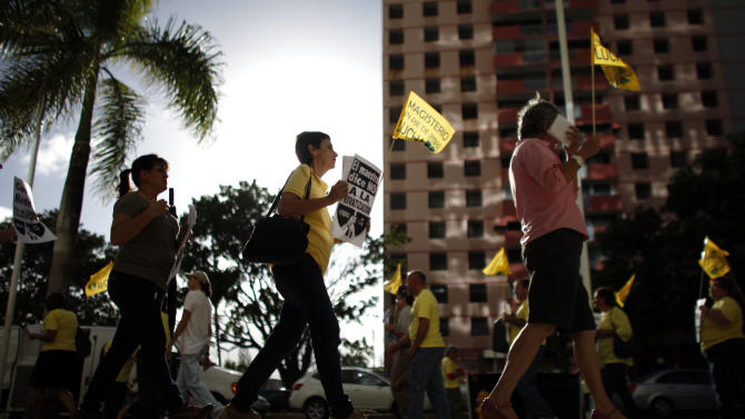 People protest outside the government pension headquarters in San Juan, Puerto Rico, Wednesday, Jan. 30, 2013. Puerto Rico is confronting what economists and financial analysts say is a ticking fiscal time bomb: A public pension system with a $37.3 billion unfunded liability that must be addressed soon. Nearly three years ago, former Gov. Fortuno established a committee charged with solving the pension fund's fiscal problems, noting that the overall system was paying $679 million more a year than what it received in contributions. (AP Photo/Ricardo Arduengo)
