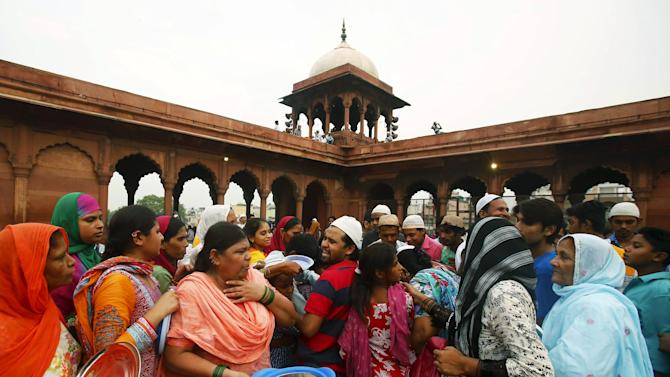 Muslim men and women gather to receive their free Iftar meal during the holy month of Ramadan at the Jama Masjid of Delhi