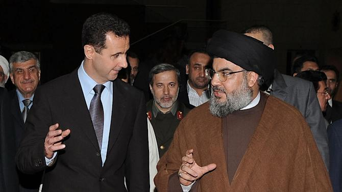 """FILE -- In this Thursday February 25, 2010 file photo, released by the Syrian official news agency SANA, Hezbollah leader sheik Hassan Nasrallah, right, speaks with Syrian President Bashar Assad, left, upon their arrival for a dinner, in Damascus, Syria. The powerful alliance of Iran, Syria and militant groups Hezbollah and Hamas, once dubbed the """"Axis of Resistance,"""" is fraying. Iran's economy shows signs of distress from nuclear sanctions, Syria's president is fighting for his survival, Hezbollah is under fire by Lebanese who blame it for the assassination of an anti-Syrian intelligence official and Hamas _ the Palestinian arm _ has bolted. (AP Photo/SANA, File)"""