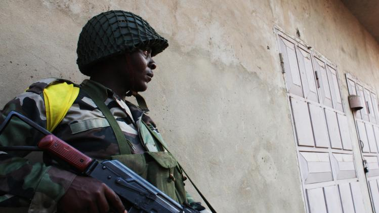 An Africa Union peacekeeping soldier takes a strategic position to quell street violence in neighbourhoods in Bangui