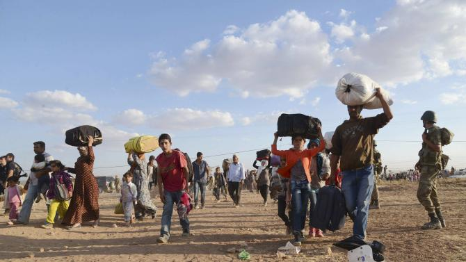 Syrian Kurds walk with their belongings after crossing into Turkey at the Turkish-Syrian border, near the southeastern town of Suruc in Sanliurfa province
