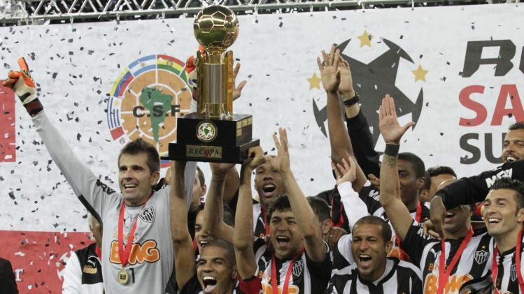 Silva of Atletico Mineiro holds up the trophy as he celebrates with team mates after defeating Lanus in their Recopa Sudamericana final soccer match in Belo Horizonte