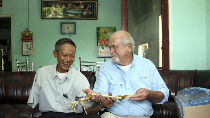 Dr. Sam Axelrad, right, hands over arm bones belonging to former North Vietnamese soldier Nguyen Quang Hung, left, at Hung's house in the town of An Khe, Gia Lai province, Vietnam on Monday July 1, 2013. In October 1966 Axelrad amputated Hung's arm after the soldier was shot in the arm in an ambush by American troops in the coastal province of Binh Dinh in the former South Vietnam. After decades of silence, the two veterans resumed contact after a Vietnamese journalist wrote an article in a newspaper last year about Axelrad's search for Hung, prompting Hung's brother in law to contact the newspaper's editors. (AP Photo/Thanh Nien Newspaper, Kha Hoa)