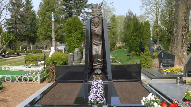 FILE This April 26, 2011 file photo taken in southern Lithuania shows the grave of Drasius Kedys, a Lithuanian man who died in April 2010 after alleging that his daughter, Deimante, at the time nearly 5-years-old, had fallen prey to a pedophile ring. Drasius Kedys launched a bloody vendetta against an alleged pedophile network of judges and politicians that he claimed preyed on his then 5-year-old daughter. Experts say the dispute, which has become a national obsession, reflects deeper currents of discontent in a post-Soviet society plagued by emigration and the world's highest suicide rate. (AP Photo)