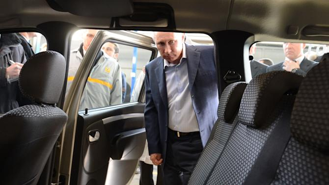 In this Wednesday, April 4, 2012 file photo, Russian Prime Minister Vladimir Putin examines inside of a Lada Largus car while visiting the Avtovaz plant, Russia's biggest car maker, in the southern city of Togliatti on the Volga River. Car makers Renault-Nissan on Thursday, May 3, 2012,  signed a deal with a Russian state-owned corporation that delayed their move to acquire a controlling stake in Russian car producer Avtovaz to 2014.  (AP Photo/RIA-Novosti, Alexei Druzhinin, Government Press Service)