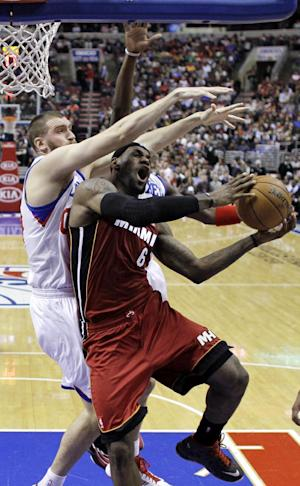 Miami Heat's LeBron James (6) tries to get a shot past Philadelphia 76ers' Spencer Hawes, left, and Jrue Holiday in the first half of an NBA basketball game, Wednesday, March 13, 2013, in Philadelphia. (AP Photo/Matt Slocum)