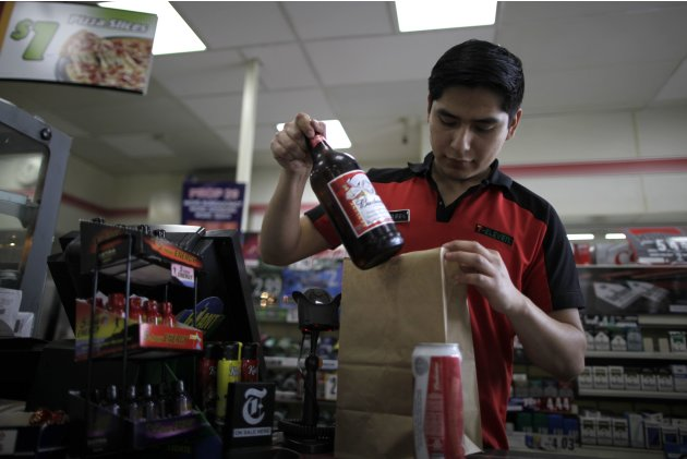 Abel Santiago, 21, serves a customer at a 7-Eleven convenience store in Santa Monica, California