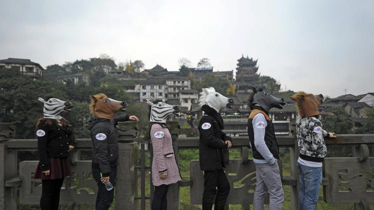 Participants wearing horse and zebra head masks line up as part of an artistic performance in Chongqing