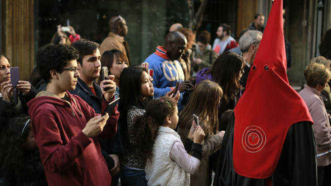 "People observe a penitent as she takes part in the procession of ""La Soledad"" during Holy Week in Madrid, Spain, Saturday, March 30, 2013. Hundreds of processions take place throughout Spain during the Easter Holy Week. (AP Photo/Andres Kudacki)"