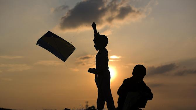 Pakistani children who are displaced from their villages with families due to fighting between security forces and militants fly kites in a suburb of Islamabad, Pakistan, Tuesday, July 28, 2015. (AP Photo/B.K. Bangash)