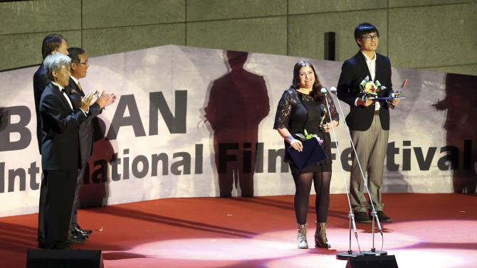 "Director Maryam Najafi, second from right, speaks after being awarded the New Currents prize during the Busan International Film Festival in Busan, South Korea, Saturday, Oct. 13, 2012. Najafi, who holds a dual citizenship in Iran and Canada, said her award-winning movie ""Kayan"" about a Lebanese single mother in Canada depicts women's universal struggles. (AP Photo/Yonhap, Jo Jung-ho) KOREA OUT"