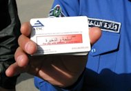 An Iraqi policeman holds an explosives detection card used in the controversial pistol shaped ADE 651 bomb detector in Baghdad in 2010. British prosecutors have charged six men with fraud for selling bomb detectors widely panned as ineffective that were sold to countries including Iraq, officials said Thursday
