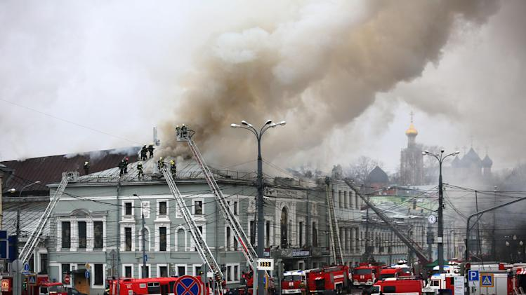 Fire fighters work at the site of a fire at the building of the School of Modern Drama theater in Moscow, Russia, Sunday, Nov. 3, 2013. The fire broke out in the attic of the building and more than 350 people were evacuated. (AP Photo/Mikhail Listopadov)