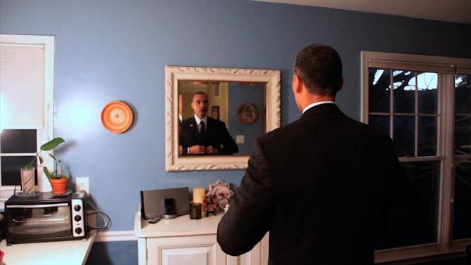 "In this image from video, President Barack Obama lookalike Larry Graves gets ready for an appearance. Graves has the security detail, the prominent ears and the U.S. flag pin, but substitute teacher Graves is no Barack Obama. He's a professional lookalike for the president. They have something else in common, too: a frantic schedule leading up to the inauguration. ""It's definitely a busy time,""  Graves said. ""Between the campaign season and the inauguration, it's been prime time. Barack Obama is a respectable guy. People want to have him at their parties."" (AP Photo)"