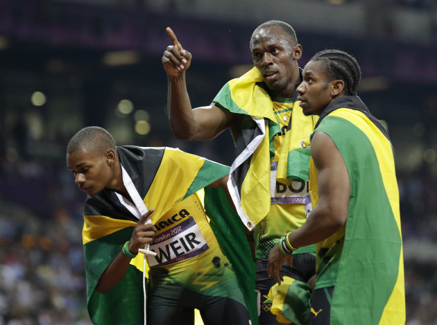 Jamaica's gold medal winner Usain Bolt, center, celebrates with his teammate Warren Weir, left, and Yohan Blake after the men's 200-meter final during the athletics in the Olympic Stadium at the 2012