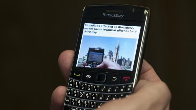 A Blackberry subscriber holds a Research in Motion Blackberry in Ottawa, Wednesday Oct. 12, 2011. Sporadic outages of BlackBerry messaging and email service spread to the U.S. and Canada on Wednesday, as problems stretched into the third day for Europe, Asia, Latin America and Africa. (AP Photo/The Canadian Press, Adrian Wyld)