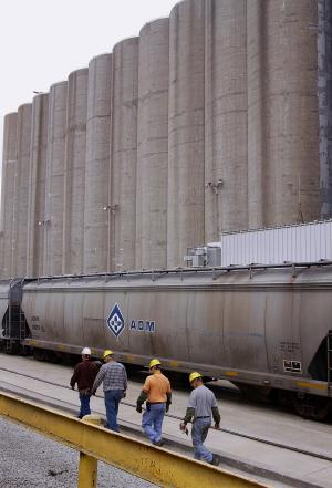 In this photo taken July, 2009, Archer Daniels Midland Company workers walk along the grain silos next to the rail car tracks at the ADM plant in Decatur, Ill.  Agribusiness conglomerate Archer Daniels Midland Co. announced plans Wednesday, Jan. 11. 2012 to cut 1,000 jobs, or about 3 percent of its total workforce, with the majority of the positions being salaried staff.   (AP Photo/Seth Perlman)