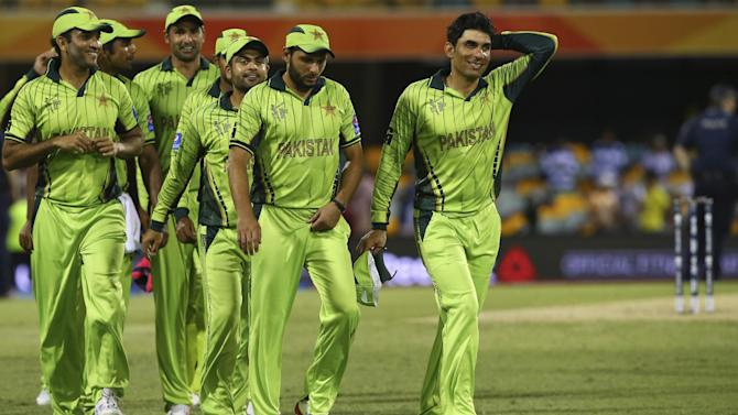 Pakistan's players led by skipper Misbah-ul-Haq, right, walk back after defeating Zimbabwe in the Pool B Cricket World Cup match in Brisbane, Australia, Sunday, March 1, 2015. (AP Photo/Tertius Pickard)